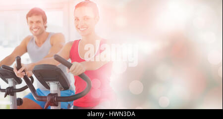 Smiling young couple working out at spinning class in a bright gym - Stock Photo