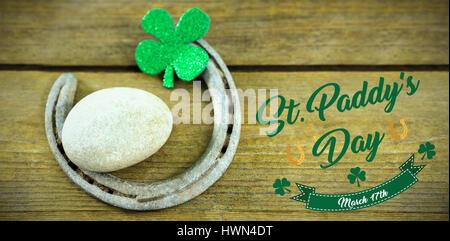 Print against st patricks day shamrocks with horseshoe and pebble - Stock Photo