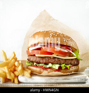 fresh tasty burger and french fries potatoes on wooden table - Stock Photo