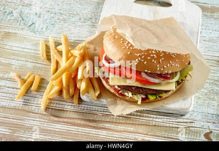fresh tasty burger on wooden table - Stock Photo