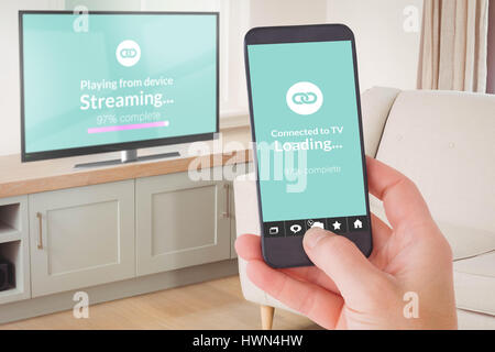 Female hand holding a smartphone against sitting room - Stock Photo