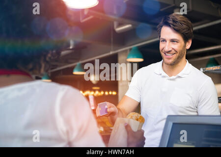 Graphic image of flare against happy customer paying by credit card for bread - Stock Photo