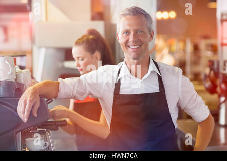Graphic image of flare against barista smiling at the camera - Stock Photo