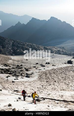 Italy, Lombardy, Temu, hikers walking along the glacial Lobbia towards the crest of Cresta Croce - Stock Photo