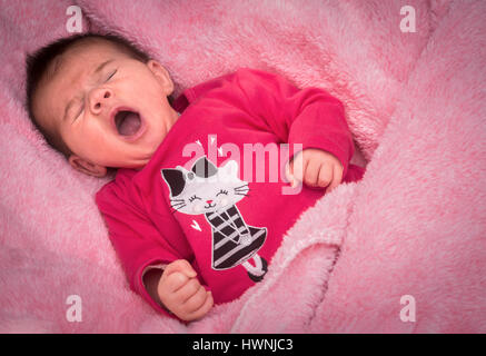 A newborn baby girl yawning on a pink blanket, certainly gazed lovingly by her parents who take advantage of the - Stock Photo