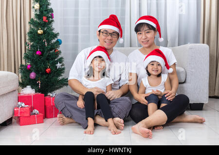 Happy Asian Chinese family sitting on the floor celebrating Christmas in the living room at home with Santa Claus - Stock Photo