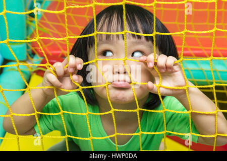 Happy Asian Chinese little girl playing behind the net at indoor playground. - Stock Photo