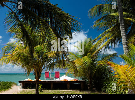 Beach Vacations: Patacho Beach, Alagoas, Brazil, considered one of the most beautiful beaches in Brazil- Beach with  a pair of red chairs. Stock Photo