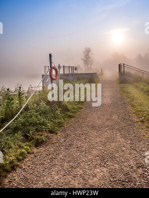 The early morning sun filters through the fog rising from the pond casting a warm glow to the stone path in Stouffville, - Stock Photo
