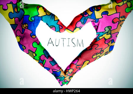 woman hands forming a heart patterned with many puzzle pieces of different colors, symbol of the autism awareness, - Stock Photo