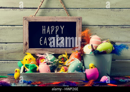 a wooden-framed chalkboard with the text happy easter hanging on a rustic wooden wall, and a pile of different decorated - Stock Photo