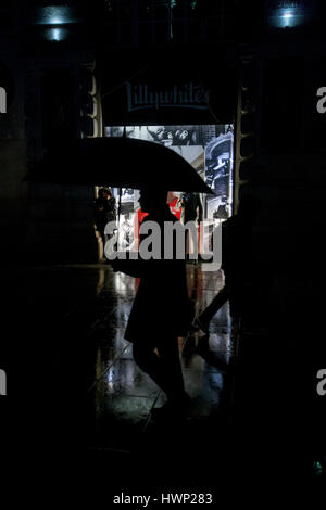 silhouetted man holding red umbrella passing lilywhites lit shop window at night in the rain - Stock Photo