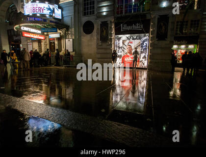 silhouetted manstanding infront of  lilywhites lit shop window at night in the rain - Stock Photo