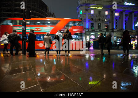 london routemaster bus in piccadilly circus people standing in the rain - Stock Photo