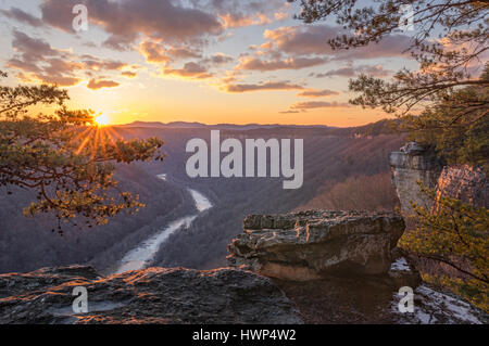 The trees yield to winter, and the setting sun highlights the craggy rim and the evergreens of the New River Gorge - Stock Photo