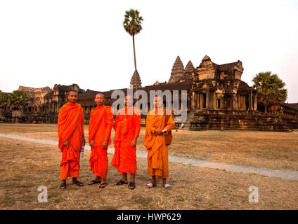 Four Buddhist monks in orange robes  pose in front of Angkor Wat - Stock Photo