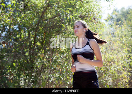 girl goes in for sports runs in forest - Stock Photo