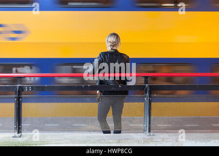 young woman in black leather coat waits on platform of railway station in the netherlands while yellow and blue - Stock Photo