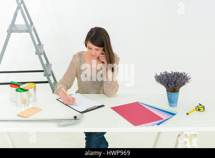Creative people workplace. Close-up view of brunette young designer woman working with colour palette at office - Stock Photo