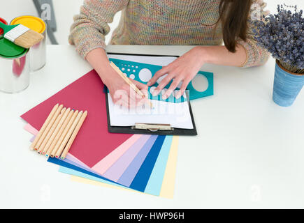Creative people workplace. Close-up view of hands of young designer woman working with colour palette at office - Stock Photo