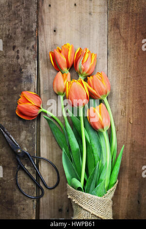 Overhead shot of a bouquet of orange and yellow tulips wrapped in burlap over a rustic wood table top with antique - Stock Photo
