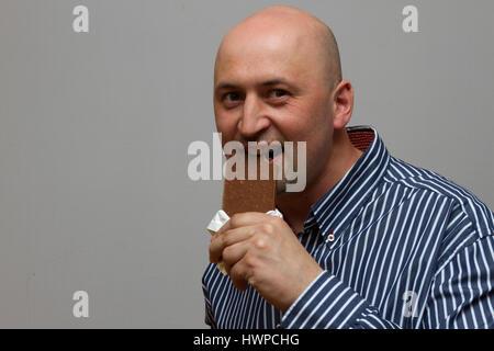 Man eating chocolate - Stock Photo