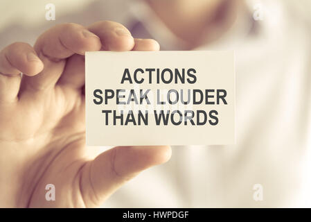 Closeup on businessman holding a card with text ACTIONS SPEAK LOUDER THAN WORDS, business concept image with soft - Stock Photo