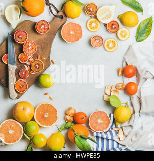 Citrus fruits slices over grey marble background, top view - Stock Photo