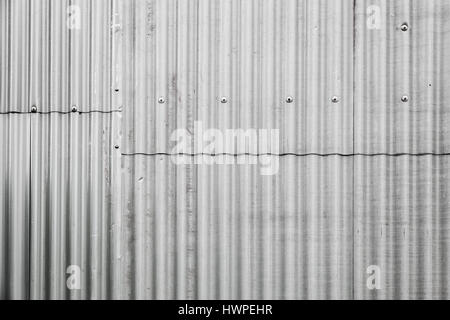 Gray corrugated metal fence made of sheets with bolts, industrial wall background photo texture - Stock Photo