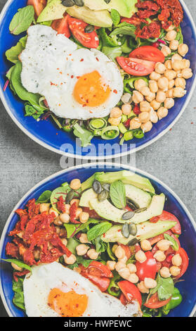 Close-up of breakfast with fried egg, chickpea, vegetables, seeds, greens - Stock Photo