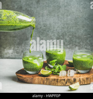 Fresh smoothie pouring from bottle with ice, mint and lime - Stock Photo