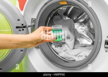 Hand pours liquid powder into the washing machine.