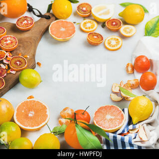 Citrus fruits slices on wooden board over grey marble background - Stock Photo