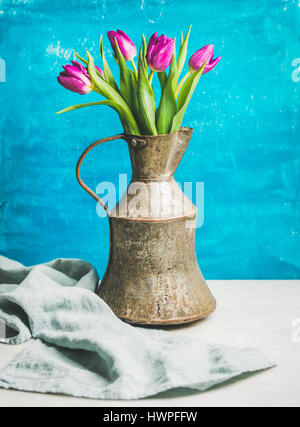 Spring purple tulips in vintage rustic copper jug, blue wall - Stock Photo