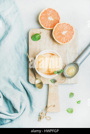 Pink grapefruit sorbet with fresh mint leaves on wooden board - Stock Photo