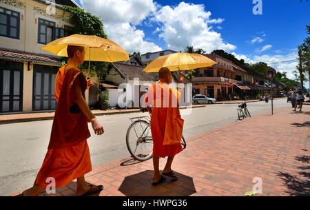 Loungprabang, Laos - August 7, 2015 : unidentified of 2 little monks are walking on the street with sun protect - Stock Photo