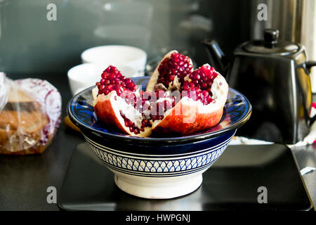 Close-up of pomegranate in plate on bowl at table - Stock Photo