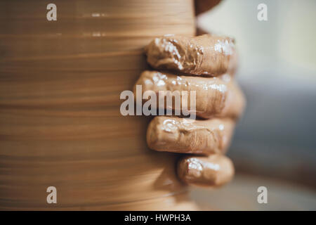 Close-up of potter's hand shaping clay at workshop - Stock Photo