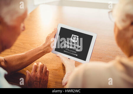 Composite image of text with wi-fi symbol against rear view of senior couple using tablet - Stock Photo