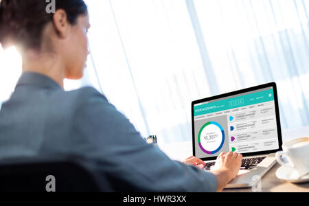 Graphic image of bank account web site against businesswoman typing on laptop - Stock Photo