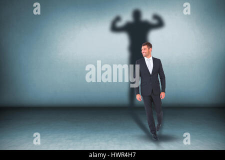 Smiling businessman standing  against grey room - Stock Photo