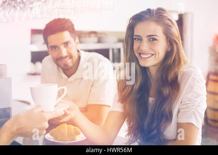 Graphic image of flare against couple eating breakfast and smiling at camera - Stock Photo