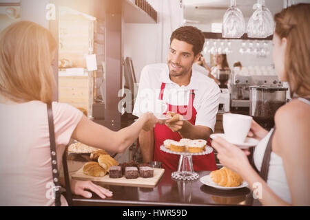 Graphic image of flare against friends with male barista at counter in coffee shop - Stock Photo
