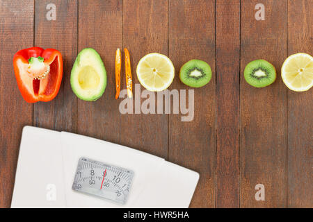 weighting scale against overhead view of various half cut vegetables and citrus fruits - Stock Photo