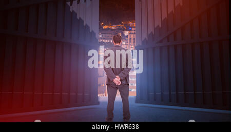 Rear view of classy businessman posing against glowing modern buildings in city 3d - Stock Photo