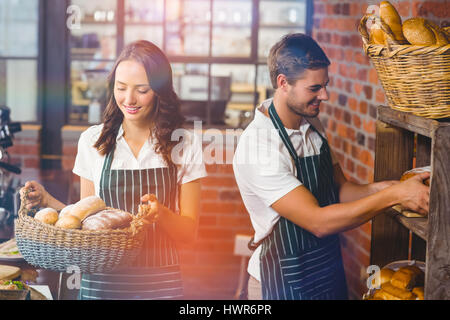 Graphic image of flare against happy co-workers working at coffee house - Stock Photo