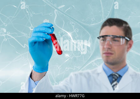 Doctor in protective glasses and surgical mask holding test tube against composite image of blue virus 3d - Stock Photo