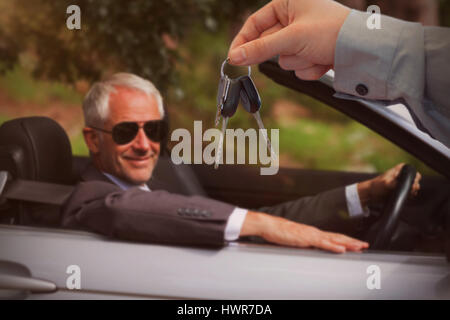 Car dealer giving keys to a customer against smiling mature businessman driving classy car - Stock Photo