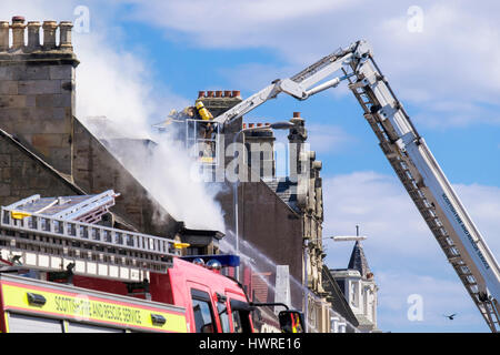 Scottish Fire and Rescue Service firefighters up a ladder fighting a blazing building. Elie and Earlsferry, Fife, - Stock Photo