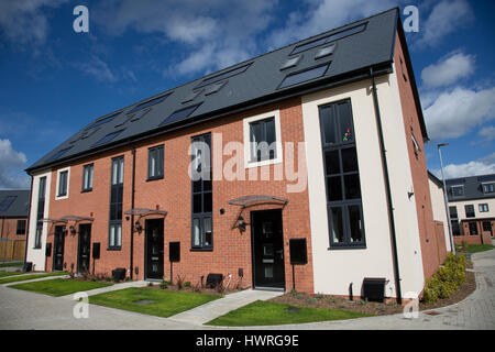 New red brick terraced houses all with solar black PV panels Persimmon Greenacres Bishops Cleeve Cheltenham UK - Stock Photo